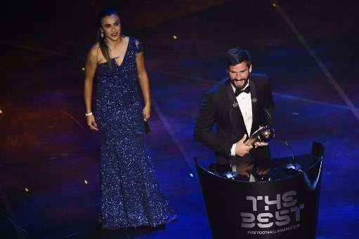 Goleiro Alisson recebeu prêmio da atacante Marta, eleita seis vezes a melhor do mundo
