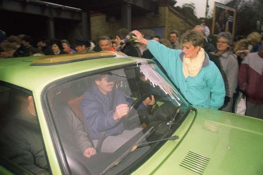 Mulher recebe moradores da Berlim Oriental enquanto  derrama Champagne em seu carro na Wollangstrasse, onde um novo ponto de passagem foi aberto em 13 de novembro de 1989