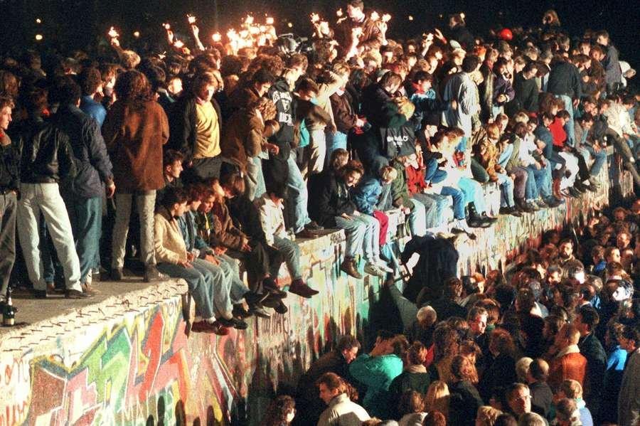 Foto de 11 de novembro de 1989 mostra jovens berlinenses do Leste comemorando no topo do Muro
