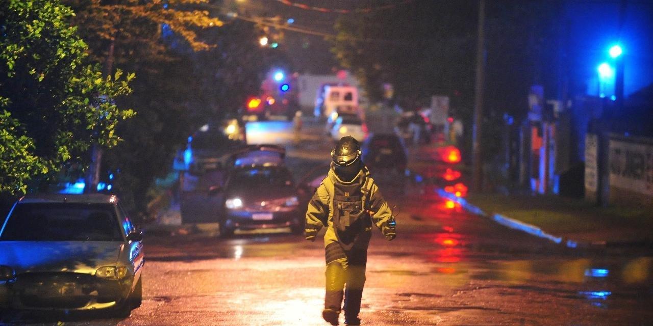 Agente do Bope, utilizando traje de proteção, retornando do veículo onde estavam os explosivos